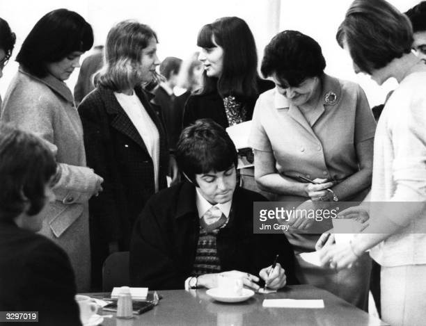 Paul McCartney singer and guitarist with the pop group The Beatles is besieged by autograph hunters in a London Transport Workers' canteen The Beatle...