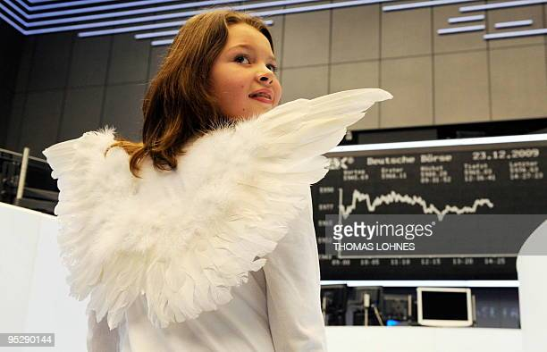 11year old Lea Sommerfeld daughter of a stock broker poses for a photo as an angel on the floor of the stock exchange in the central German city of...