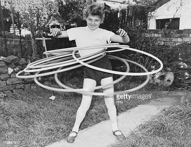 11yearold Ann Evans of Aberdare south Wales the world hula hoop marathon champion keeps seven hoops twirling simultaneously 17th November 1958