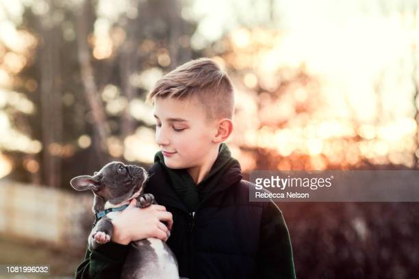 11-year-old boy and French Bulldog puppy looking at one another