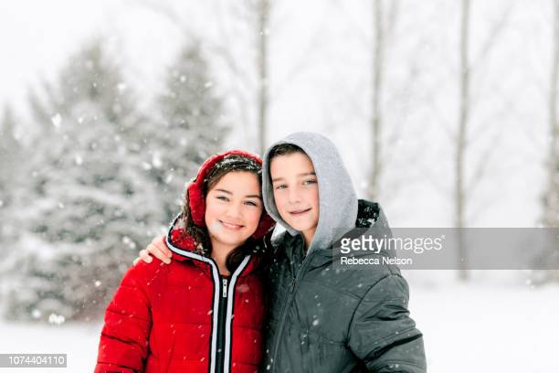 11-year-old boy and girl smiling while outside in a snowstorm
