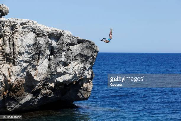 11yearold boy jumping from a cliff into the sea in Salento Italy