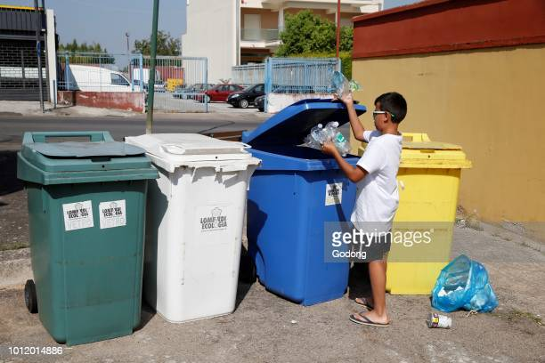 11yearold boy throwing garbage into recycling bins in Salento Italy