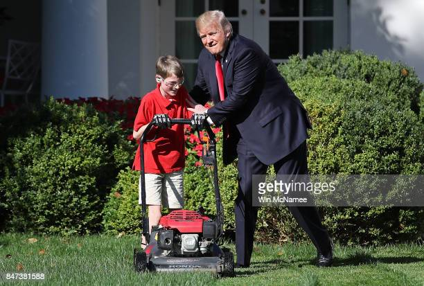 11yearold Frank FX Giaccio gets a pat on the back from US President Donald Trump while mowing the grass in the Rose Garden of the White House...