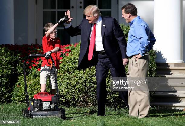 11yearold Frank 'FX' Giaccio high fives US President Donald Trump while mowing the grass in the Rose Garden of the White House September 15 2017 in...