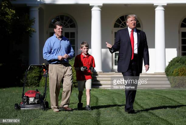 11yearold Frank 'FX' Giaccio walks with US President Donald Trump while mowing the grass in the Rose Garden of the White House September 15 2017 in...
