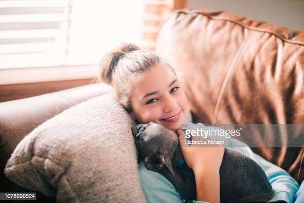 11-year-old girl lying on sofa and holding a French Bulldog puppy