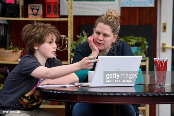 Year-old Lucas sits with his mother Fiona as she helps him with online lessons, set by his school following the national school closures due to the...