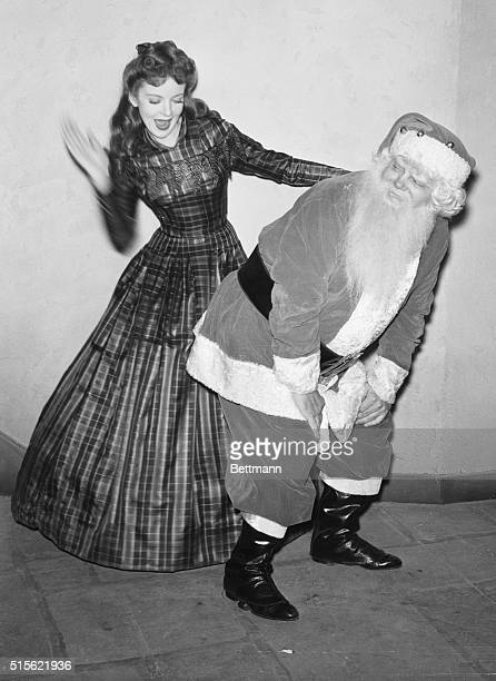 Hollywood CA Ida Lupino Warner Brothers star delivers a few wallops to Santa Claus' spankable rear extremity for although you would never guess it...