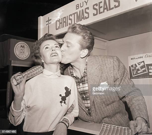 Hollywood CA Lucky customerChris Paul gets a steller kiss on the cheek from movie star Kirk Douglas after she bought Christmas seals at his booth on...