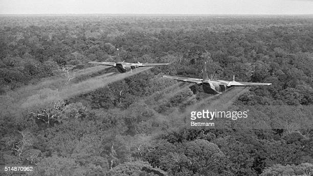 Two C123's of the 12th Air Commando Squadron fly low over heavy jungle in War Zone C spraying the canopy with defoliation Liquid The spray is being...