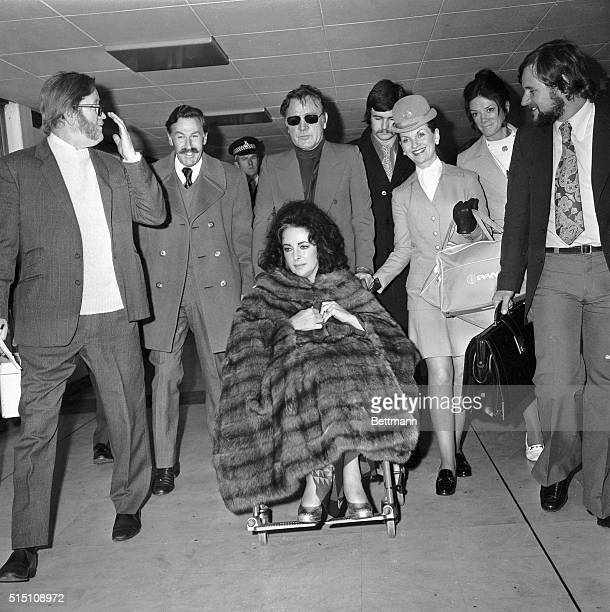 London England Wrapped up in warm fur coat Elizabeth Taylor is pushed in a wheelchair by her husband Richard Burton on their arrival at airport here...