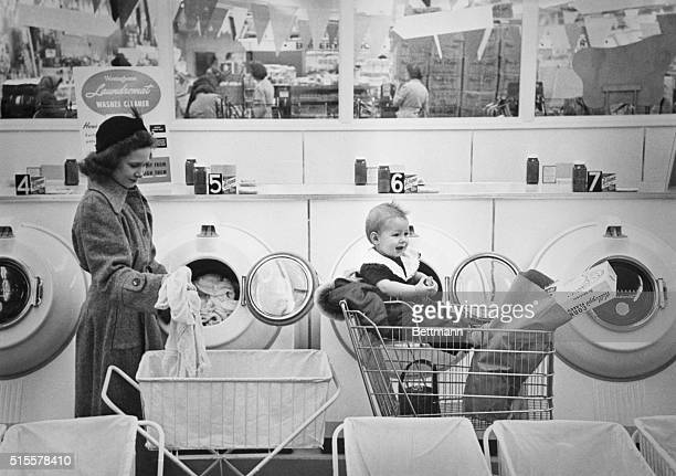 Mrs Mary Schoville takes her wash from one of the automatic washers that have been installed in the Beloit Supermarket while her oneyearold daughter...