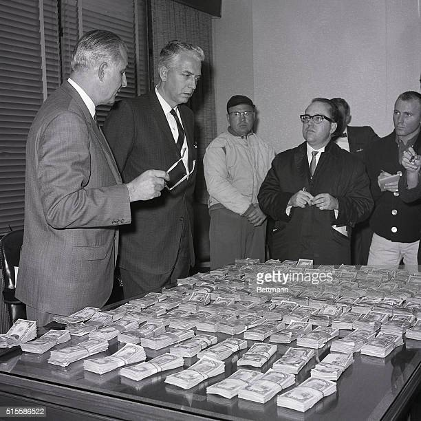 Los Angeles CA Chief FBI agent William G Simons of Los Angeles and FBI Assistant Director Joseph Casper show newsmen the money recovered with the...