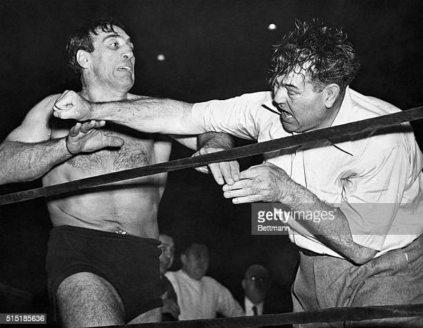 Boston, MA- Jack Dempsey , who can't resist a good fight since his days as heavyweight boxing champ of the world, takes a healthy swing at Primo...
