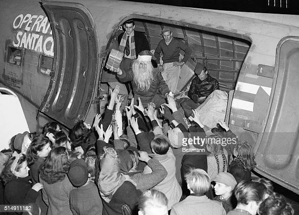 Berlin Germany Eager hands reach out toward one of St Nick's major assistants standing in the Operation Santa Claus plane at Tempelhof Airport He is...