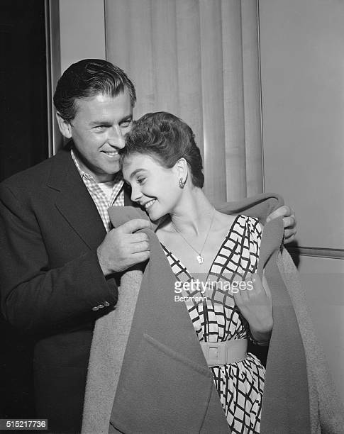 Hollywood CA With the two of them looking very loveydovey actor Stewart Granger whispers something to his bridetobe actress Jean Simmons as he helps...