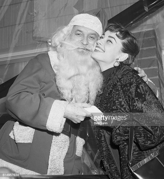 New York NY Audrey Hepburn recently named the top movie star of 1953 by Film Daily gets a kiss from Santa Claus during ceremonies at the Heart Thrift...