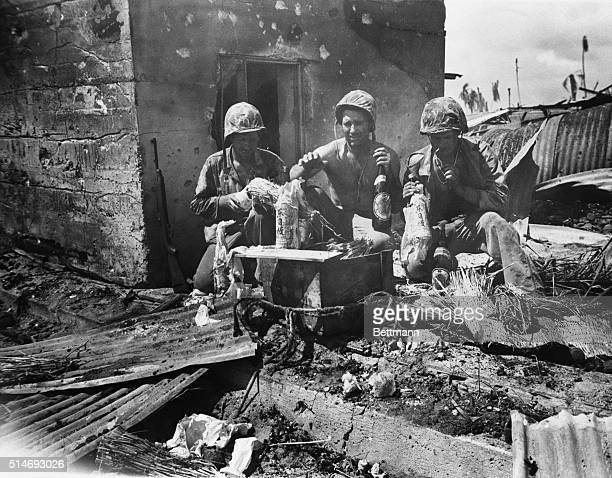 12/2/1943Tarawa Island A trio of United States Marines sample Japanese beer and sake taken from concrete strong point on Tarawa Island The former...