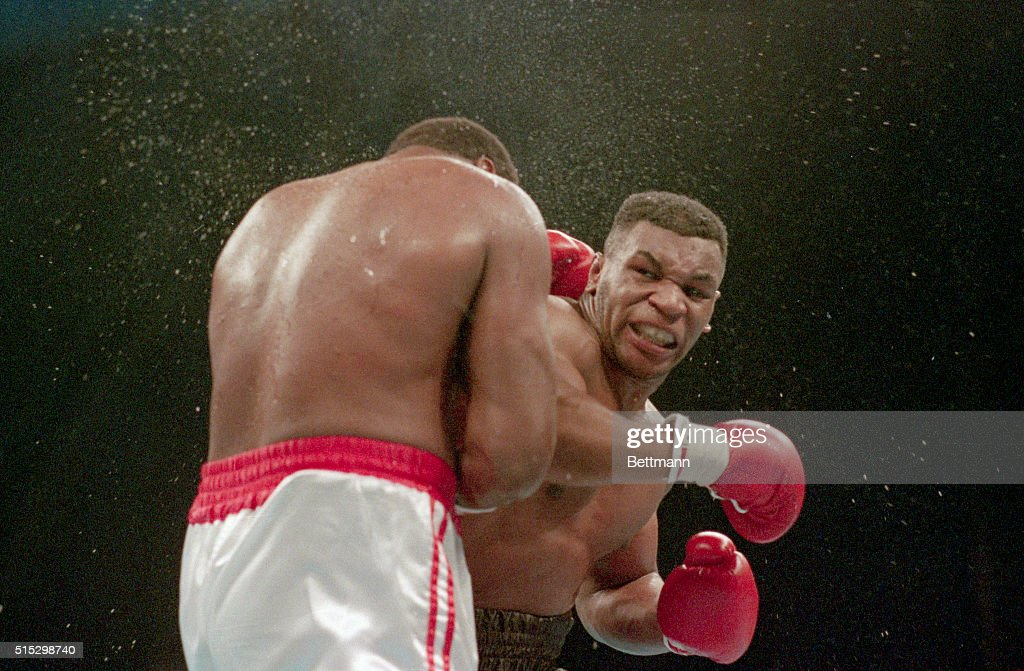 Atlantic City, NJ Ferocious faced Mike Tyson lands the knockout punch to the jaw of challenger Larry Holmes during fourth round of the World Heavyweight Championship.