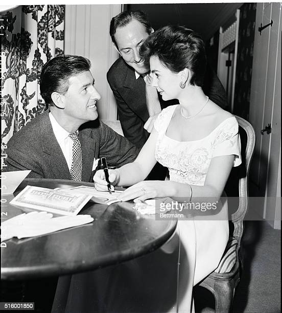 Actress Jean Simmons signs the license for her marriage to actor Stewart Granger as fellow British actor Michael Wilding looks on Wilding was best...