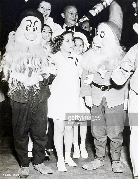12/23/37Hollywood California Escorted by two of the seven dwarfs that appear in the picture Shirley Temple child film star is pictured arriving at...
