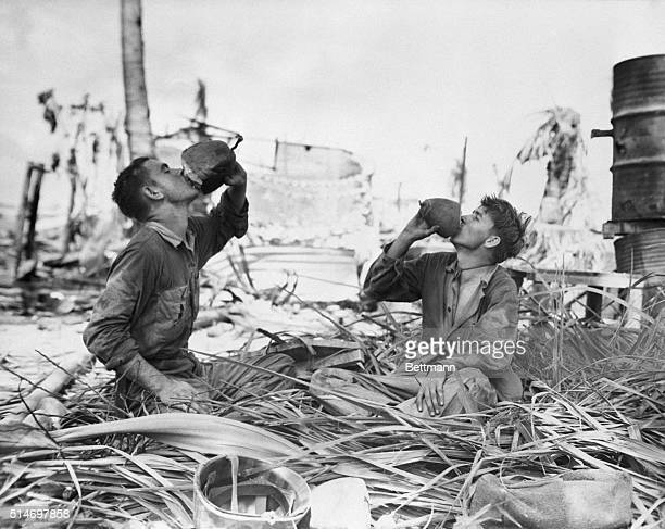 Pharmacists Matos JR Griffen of Mulberry Arkansas and EE Reynolds of Houston Texas drink coconut milk amid the desolation of battle after Tarawa...