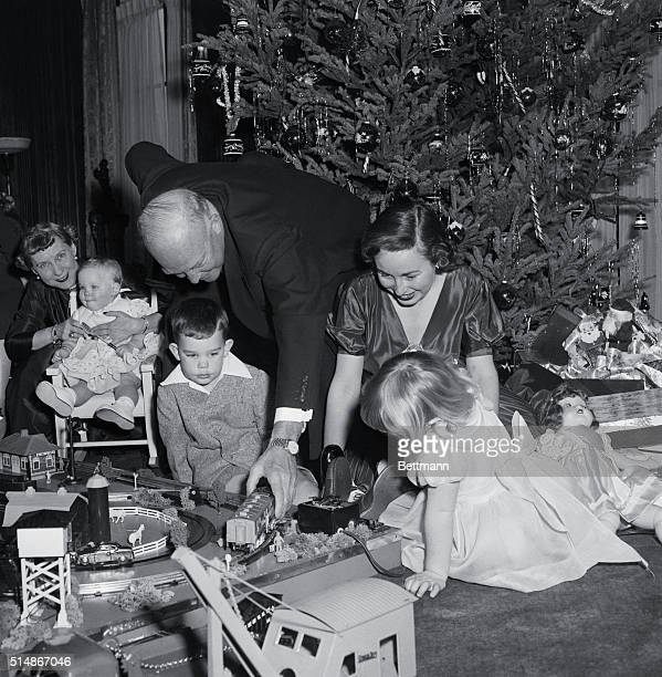 New York, NY: As the entire Eisenhower family group relaxes around the electric trains, the President-elect exercises his grandfatherly privilege of...