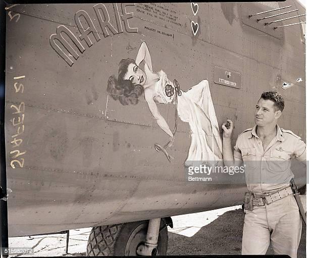 New Guinea Veteran air hero Major HM Breckt 23yearold pilot of Okmulgee OK pauses to admire 'Marie' the feminine devastator decking his bomber The...