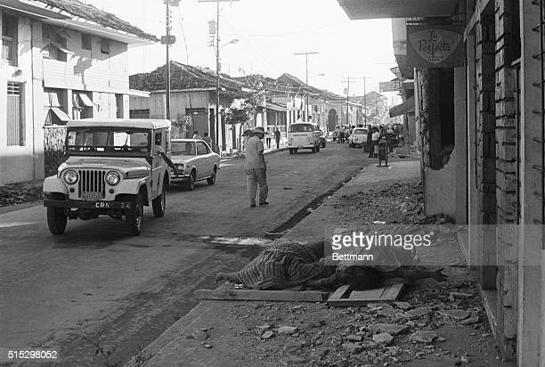 Managua Nicaragua Vehicles and pedestrians pass partially covered bodies of earthquake victims lying in the street following the disaster A major...