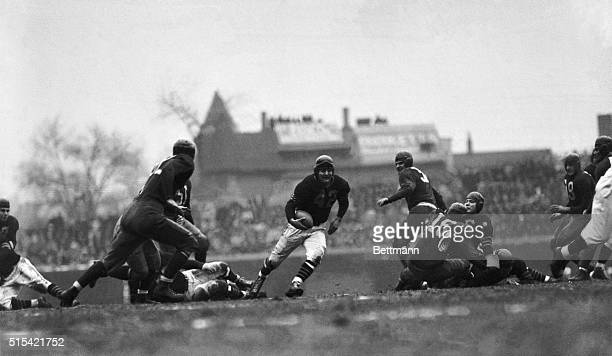 Chicago, IL - Sid Luckman, of the Chicago Bears, whose pass-tossing and work at quarter back made the star of the game, romps through a big hole for...