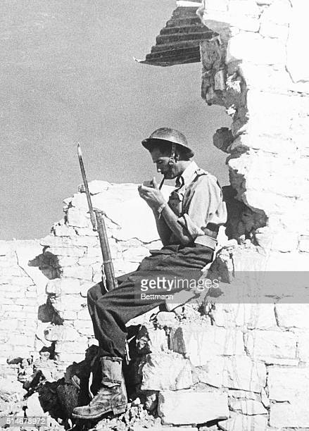 Mersa Mutruh A British Tommy who has been searching the ruins of Mersa Matruh where anything from a Nazi tank to a string og supply trucks might be...