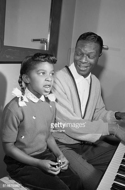 Hollywood CA Singer Nat Cole spends his spare time teaching his 7yearold daughter Sweetie to play the piano giving her voice lessons at the same time...