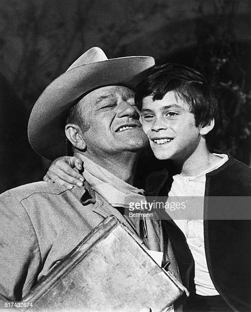 Hollywood CA John Ethan Wayne gets a hug and some good words from Dad John Wayne after filming a shootout scene with outlaws in 'The Million Dollar...