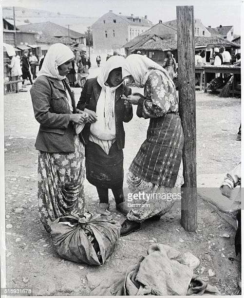 Pec Albania In the small town of Pec near the Albanian border three Moslem women stop to compare purchases from the village market in the background...