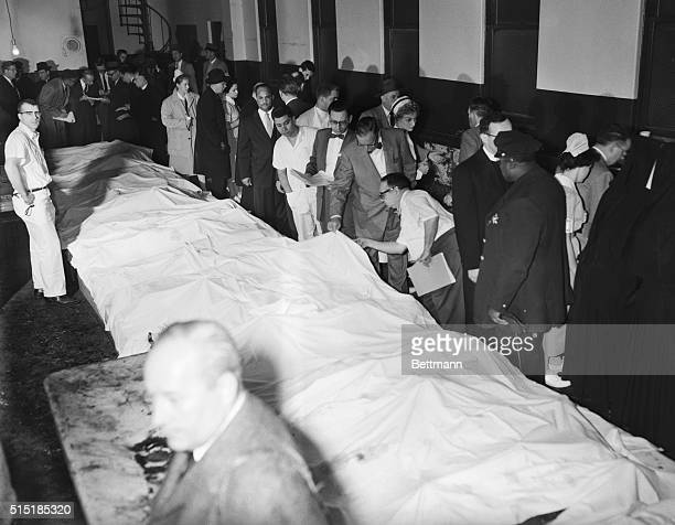 12/3/1958Chicago IL A heartbreaking task begins in Cook County Mourgue here Dec 1 as coroner Walter McCarron attempts to identify bodies of childen...