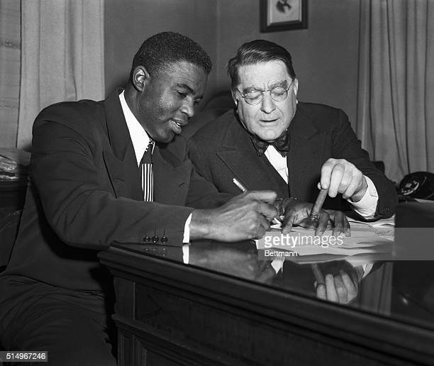 Jackie Robinson the National League's MVP in 1949 is shown signing a Brooklyn Dodger contract today as President Branch Rickey indicated the dotted...