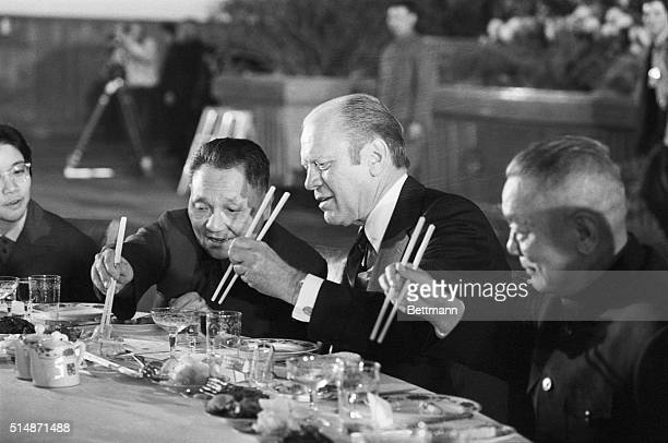 Peking, China: President Ford and Chinese Vice Premier Teng Hsiao-Ping reach for food with their chopsticks during the last banquet.