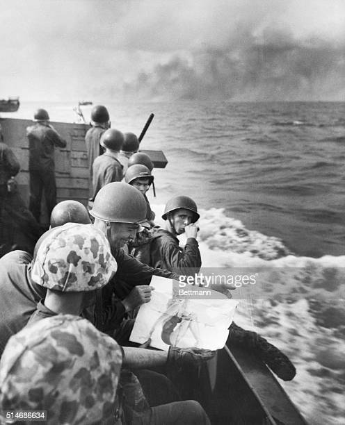 12/43As a landing barge approaches the Japheld island of Tarawa a Marine takes a last look at his picture of a pinup girl Tarawa burns in the...