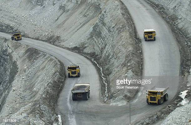 125ton Caterpillar trucks bring ore up from the bottom of the 500meterdeep Udachny diamond mine August 29 2001 in eastern Siberia Russia Udachny is...