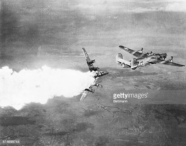 Bombs tumble from bays of this burning over turned Liberator Bomber of Major Nathan Twining's 15th Air Force as the ship breaks in two after being...