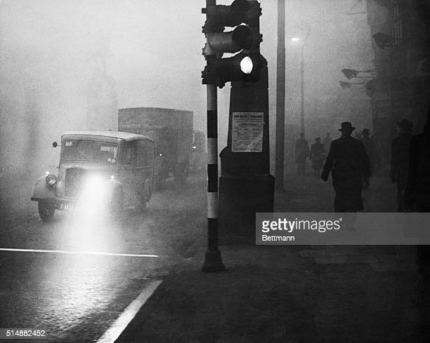 12/6/1953London England Traffic moves slowly with lights aglow as smog descends over British capital during daytime hours