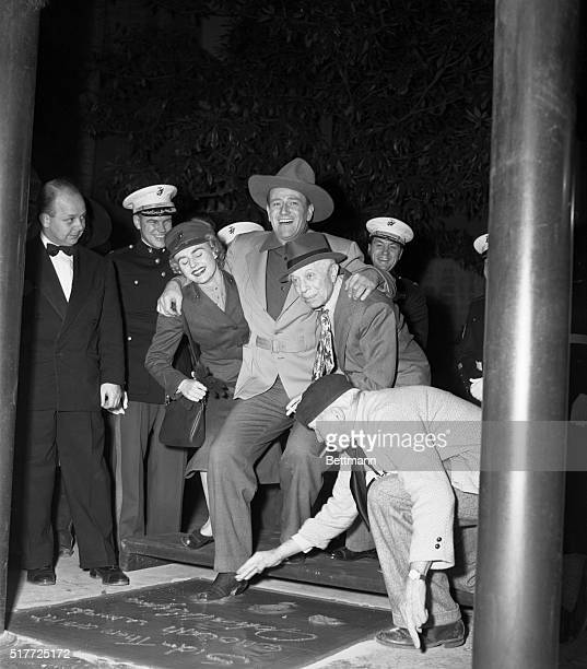 Hollywood, California: Movie actor John Wayne is aided by Marine Pvt. Inga Boberg and Sid Grauman as he puts his foot into the cement in the court of...