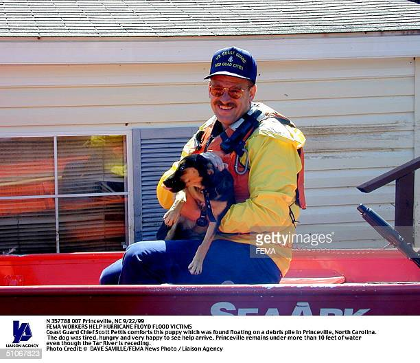 1292Nc-092299-Dscn073 Princeville, Nc 9/22/99 Coast Guard Chief Scott Pettis Comforts This Puppy Which Was Found Floating On A Debris Pile In...