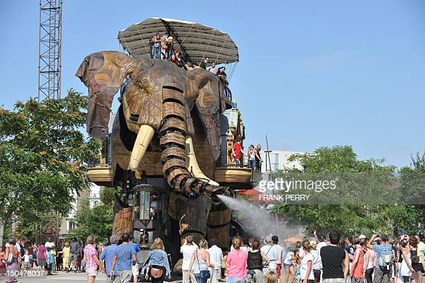 A 12metre high mechanical elephant made of steel and wood sprays water from its trunk over children and adults on August 19 at the site of Les...