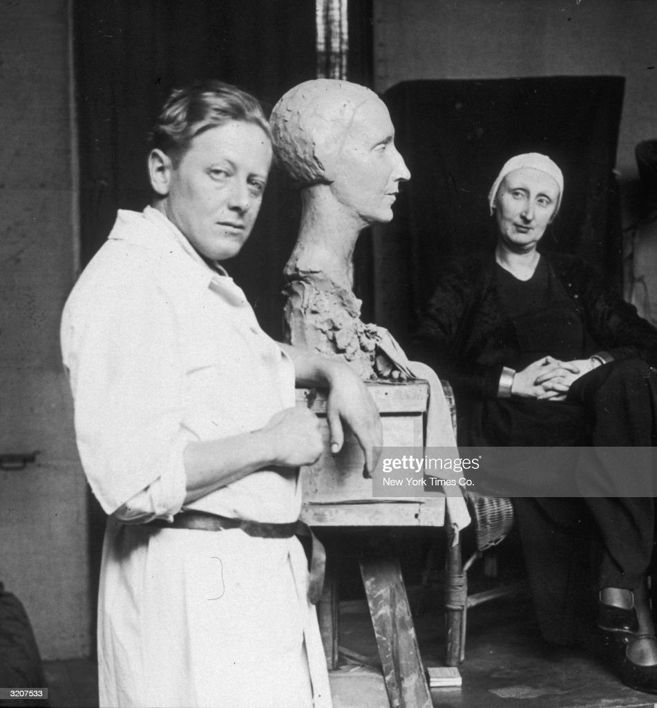 A portrait of American sculptor G Fite Waters leaning next to the bust of writer Edith Sitwell upon which he is working, while Sitwell sits in the background looking at her likeness with her head tilted and hands folded in her lap in Waters' studio, Paris, France.
