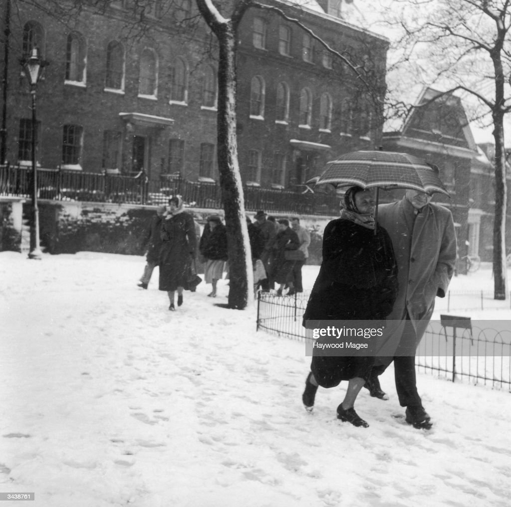 People hurrying through the spring snow. Original Publication: Picture Post - 5831 - Here Comes Spring - pub. 1952