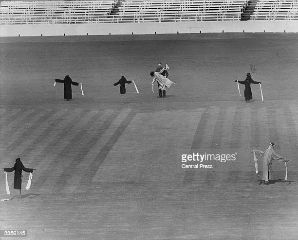 Bert Lock, head groundsman at the Oval cricket ground, putting up scarecrows to prevent pigeons mobbing him as he prepares the pitch for the county...