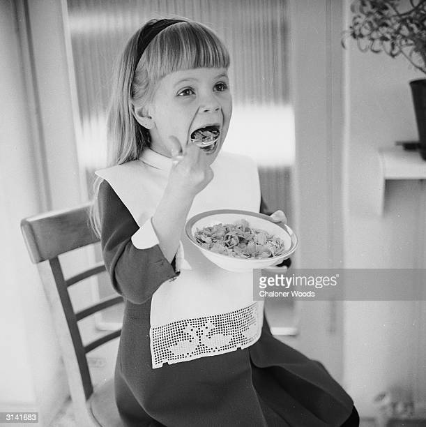A little girl wears a pretty bib in order to eat a bowl of cereal without spillage