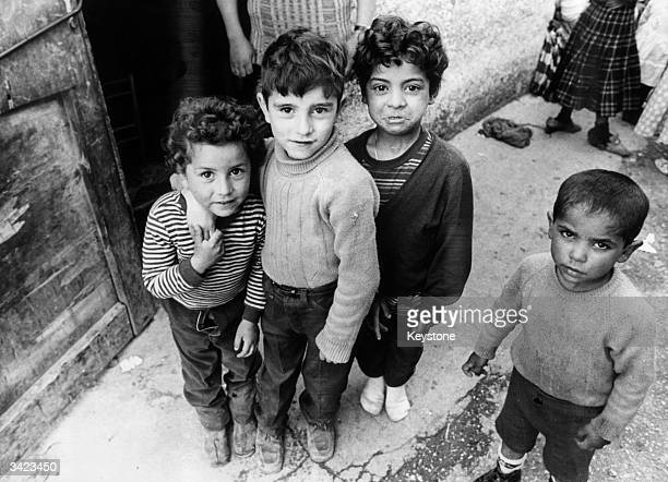 Four young Gypsy children standing together on the streets of Rome